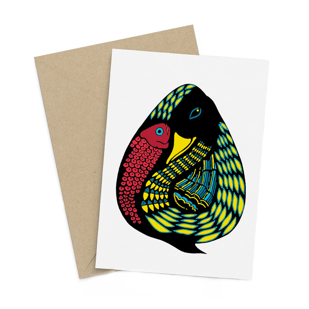 Stylized, blue and yellow duck with a red fish on a white greeting card. A brown envelope is in the background.