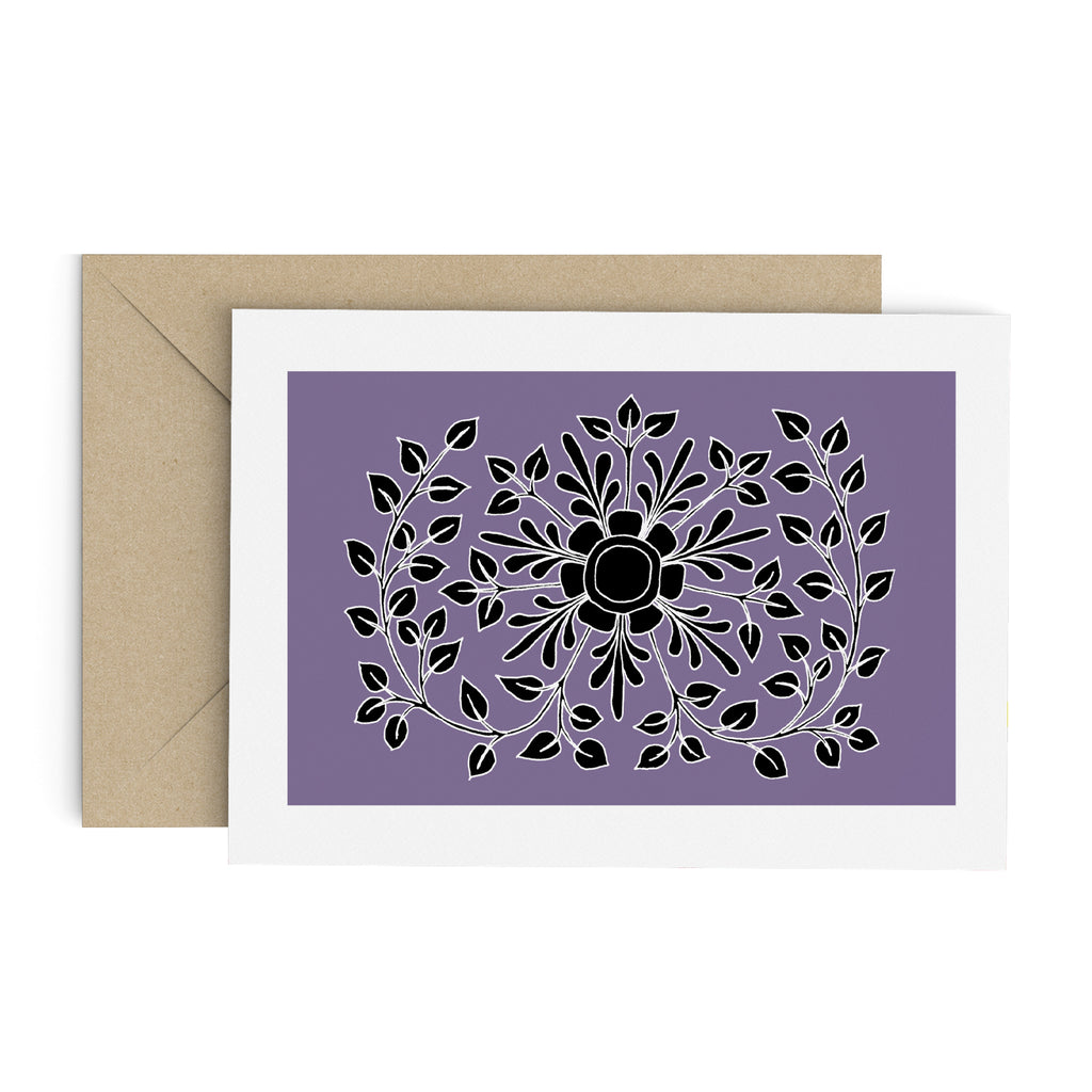 Black leafy folk flower drawing on a purple greeting card with a white border. A brown envelope is in the background.