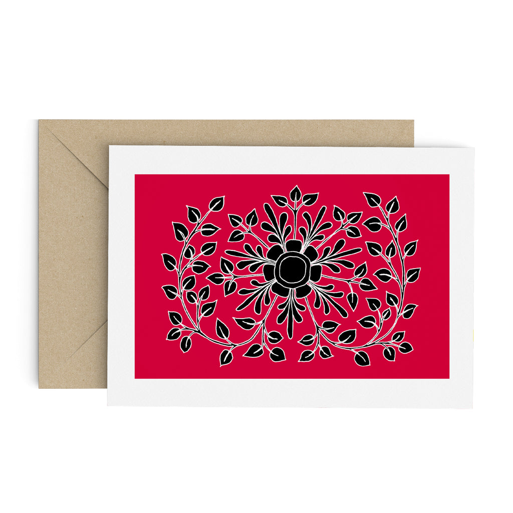 Black leafy folk flower drawing on a red greeting card with a white border. A brown envelope is in the background.