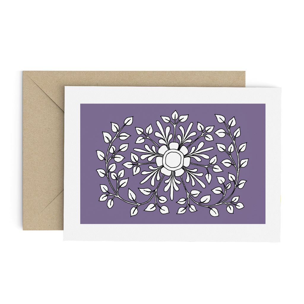 White leafy folk flower drawing on a purple greeting card with a white border. A brown envelope is in the background.