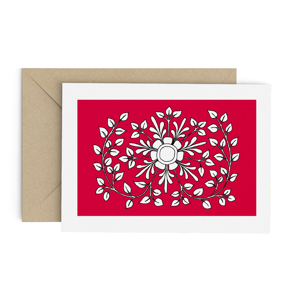 White leafy folk flower drawing on a red greeting card with a white border. A brown envelope is in the background.