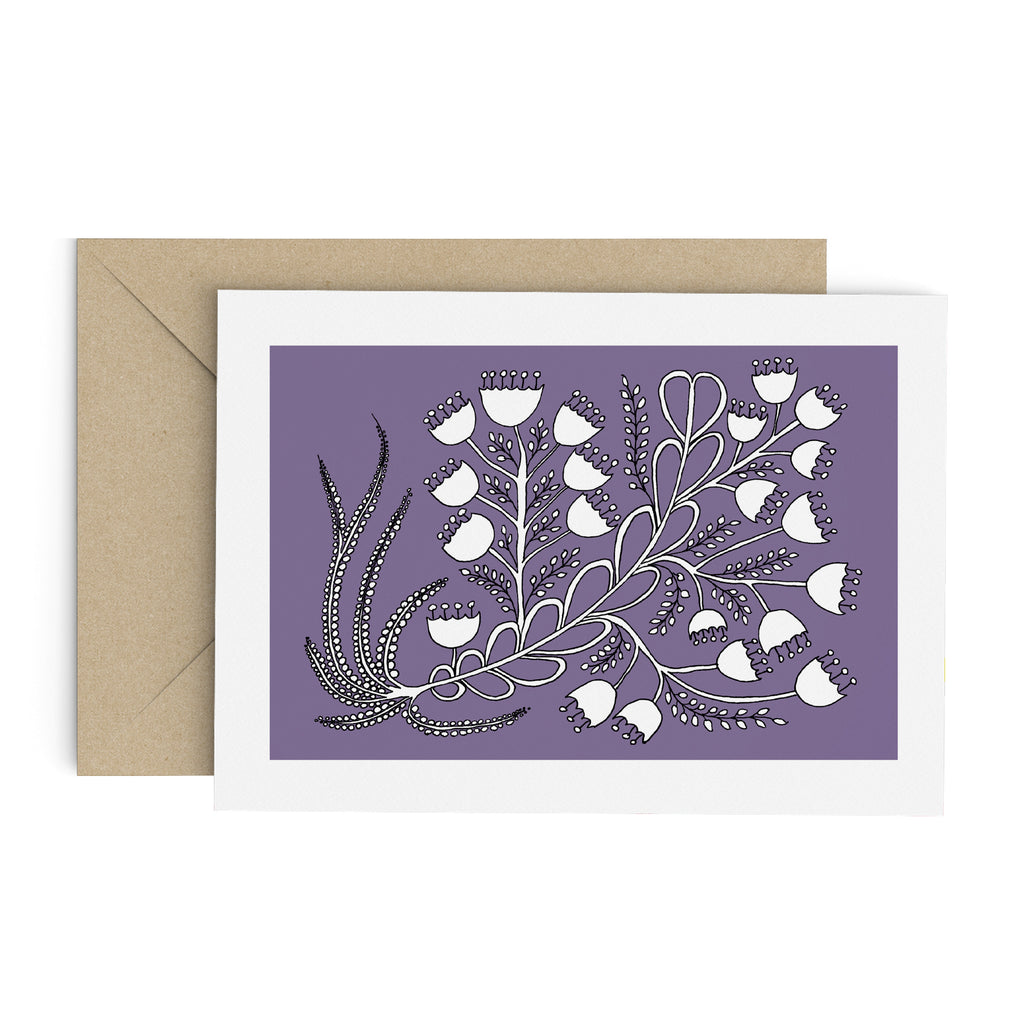 White bell flower bouquet drawing on a purple greeting card with a white border. A brown envelope is in the background.
