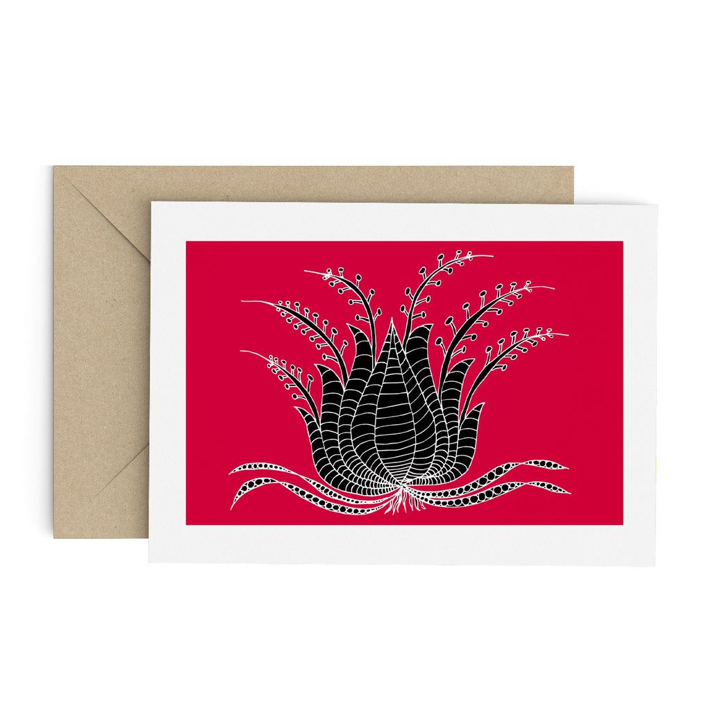 Drawing of a black succulent-like plant on a red greeting card with a white border. A brown envelope is in the background.