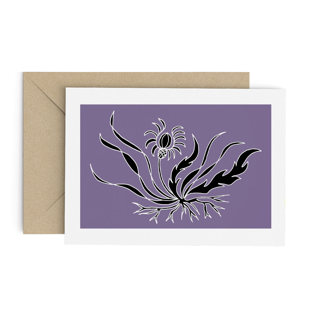 Drawing of a black flower with long, flowing leaves on a purple card with a white border. Brown envelope is in the background