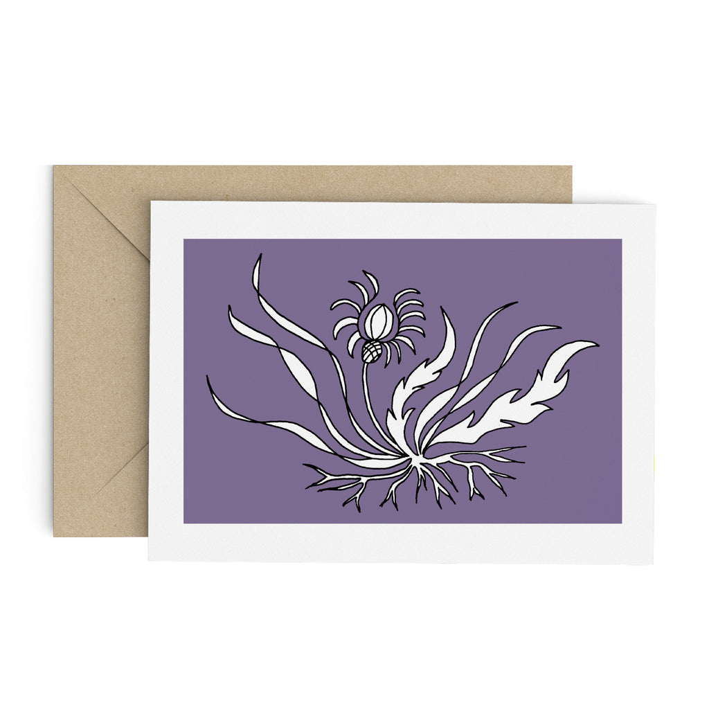 Drawing of a white flower with long, flowing leaves on a purple card with a white border. Brown envelope is in the background