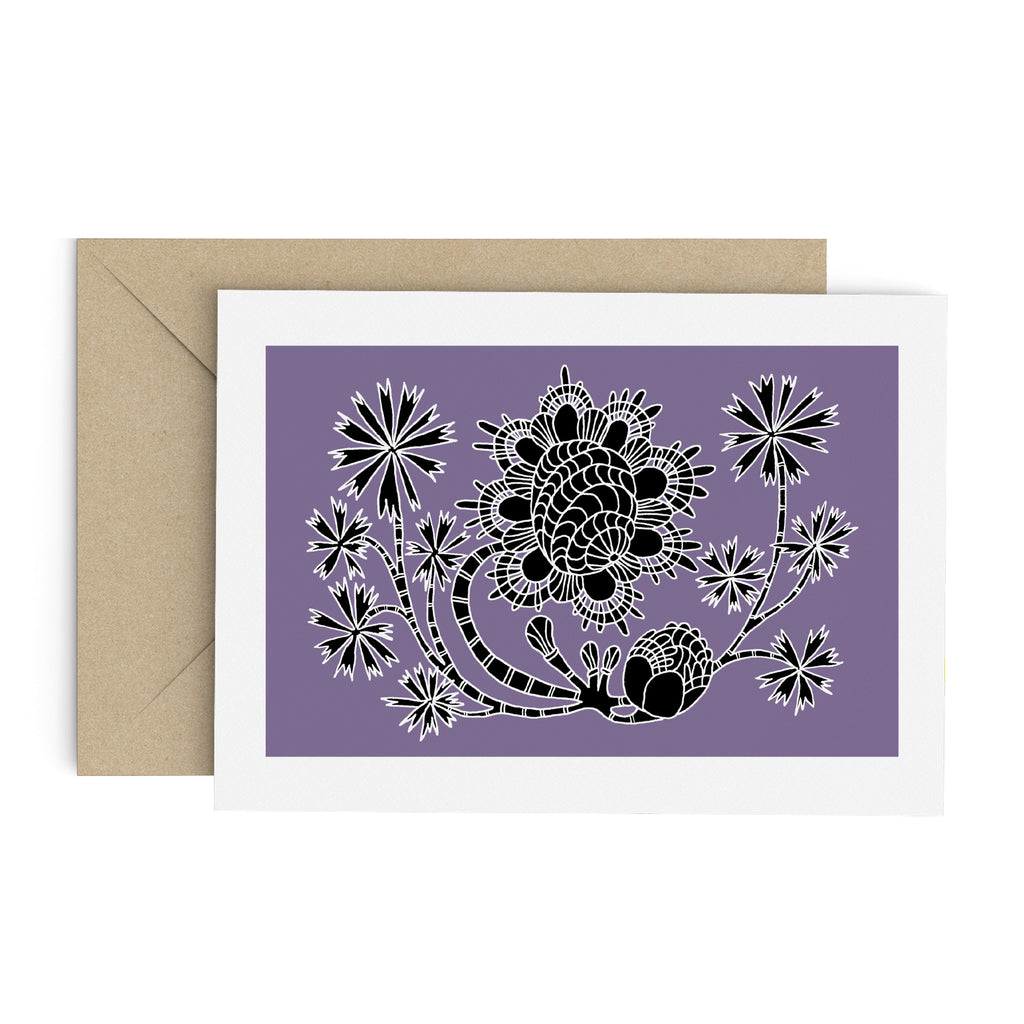 Drawing of a funky flower with palm-like leaves on a purple card with a white border. A brown envelope is in the background.