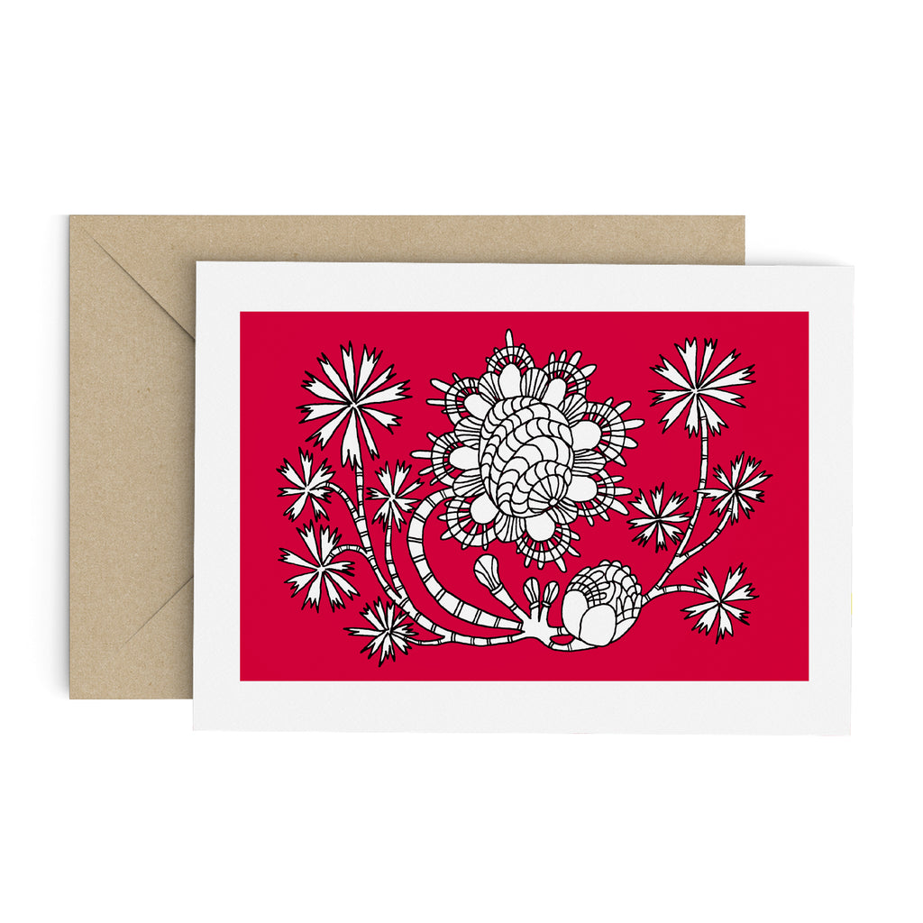 Drawing of a funky flower with palm-like leaves on a red card with a white border. A brown envelope is in the background.
