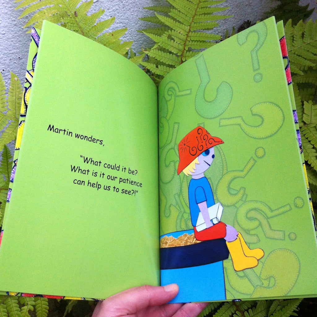 Hand holding a kids book open with a fern in the background. Boy in an orange hat is sitting on top of a big blue flower pot