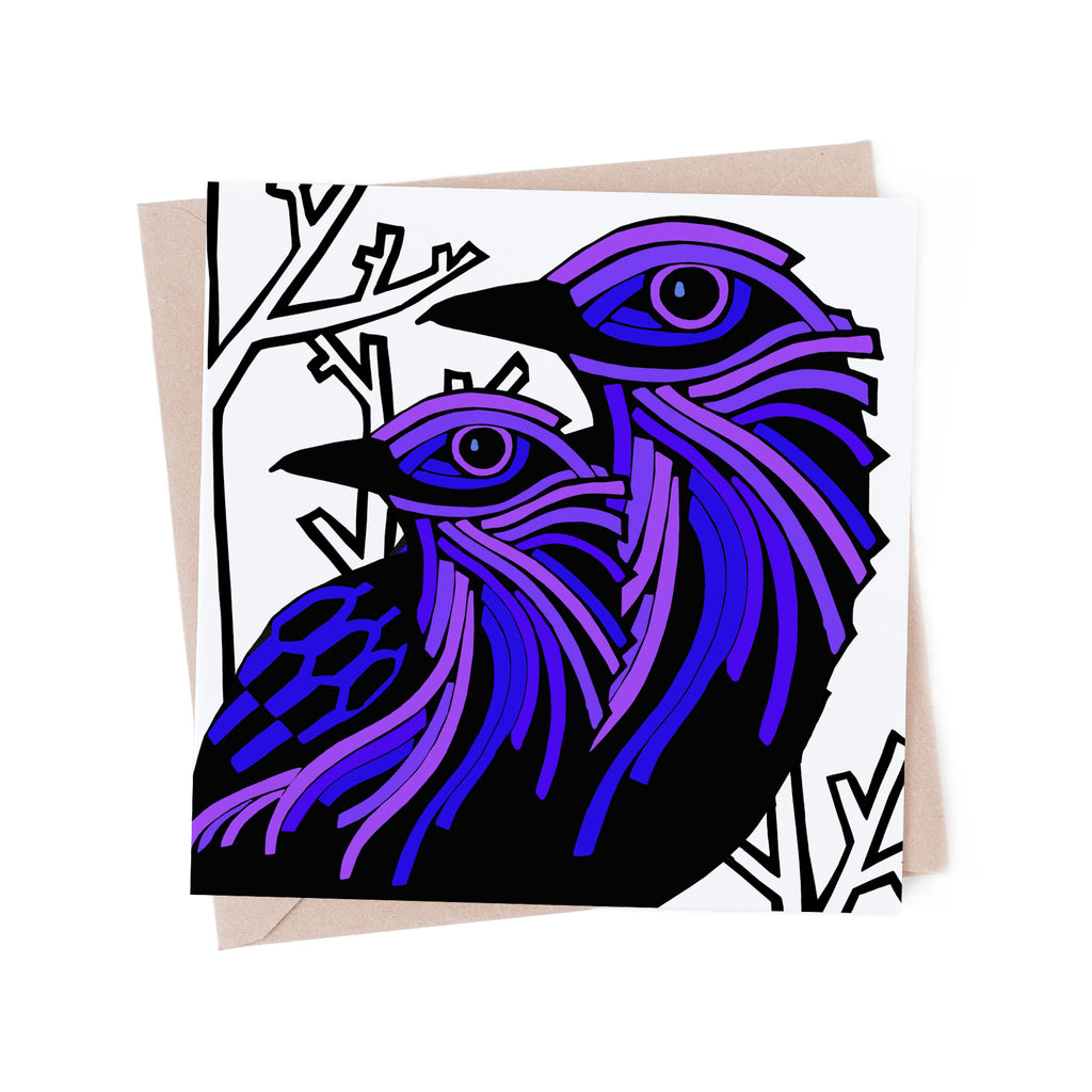 Square greeting card with two purple, stylized birds with a bare, white, winter tree. Brown envelope in the background
