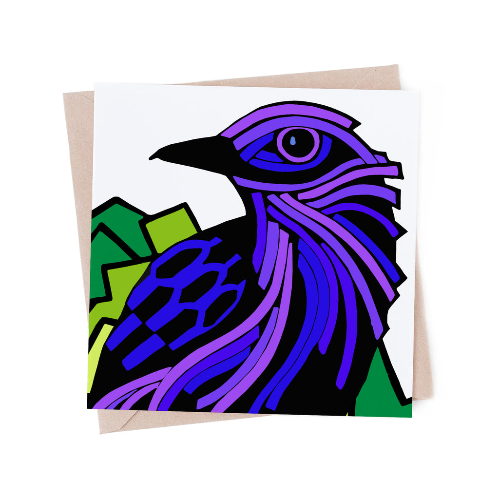 Square greeting card with a stylized, purple bird with a green tree. There is a brown envelope in the background.