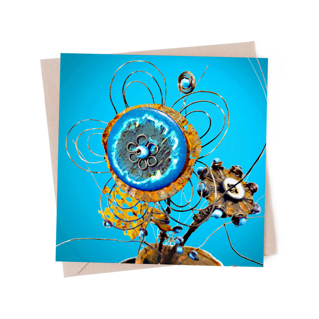 Wire sculpture of flower made with a wooden button and bits of rusty metal, on a blue greeting card.
