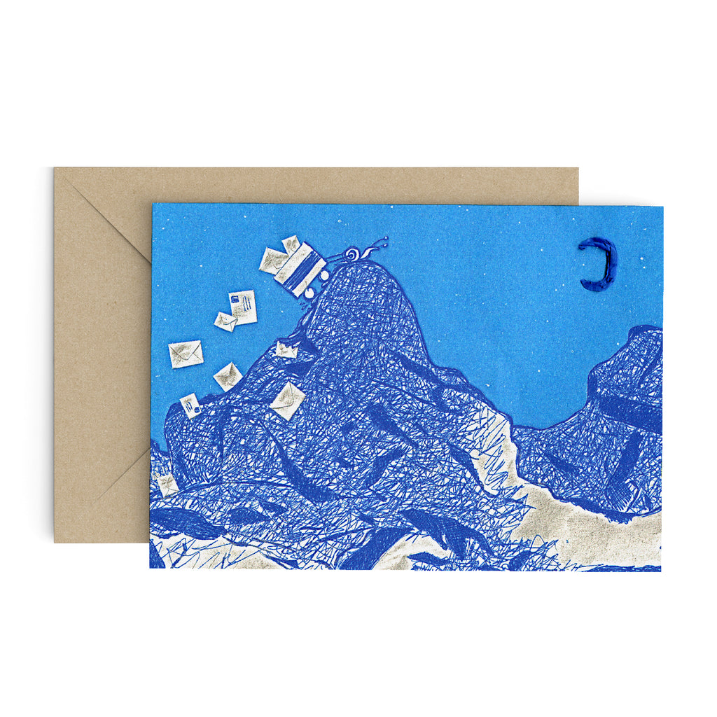 A wee little snail pulling a cart full of mail over a mountain top on a blue greeting card. There is a blue moon in the sky