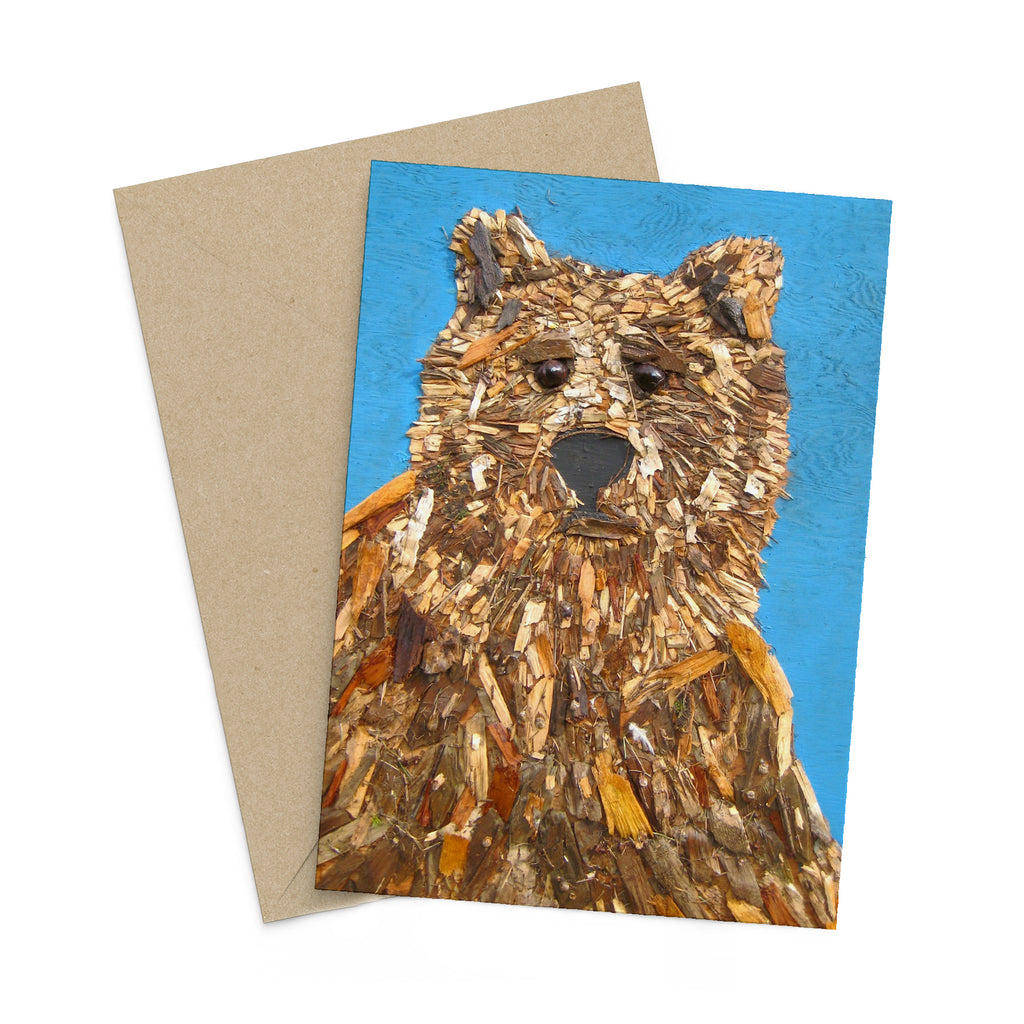 Blue portrait style greeting card with a bear made of woodchips on it. There is a brown envelope in the background.