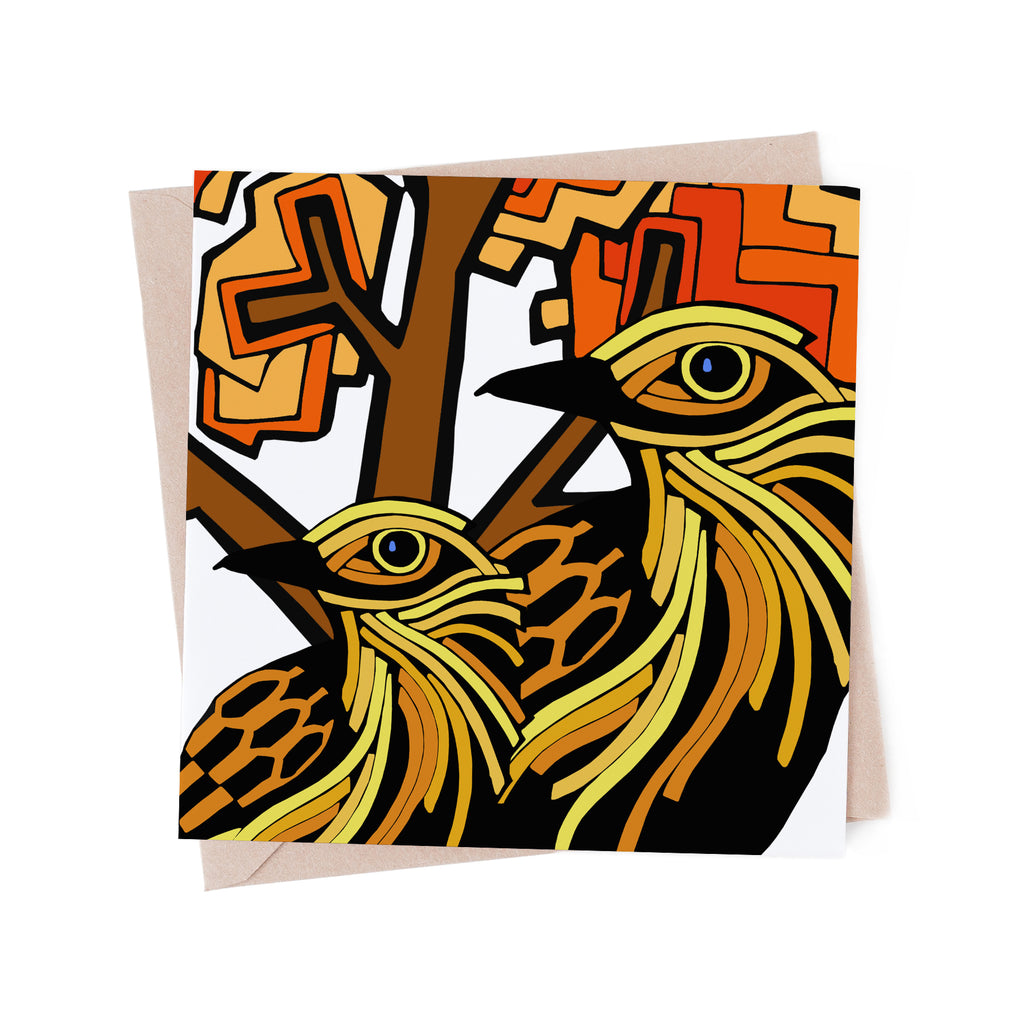 Square greeting card with stylized, yellow birds with an orange tree. There is a brown envelope in the background.