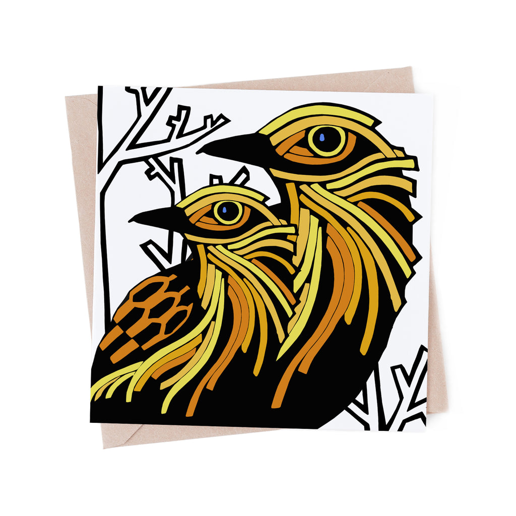 Square greeting card with yellow, stylized birds near a bare, white, winter tree. Brown envelope in the background