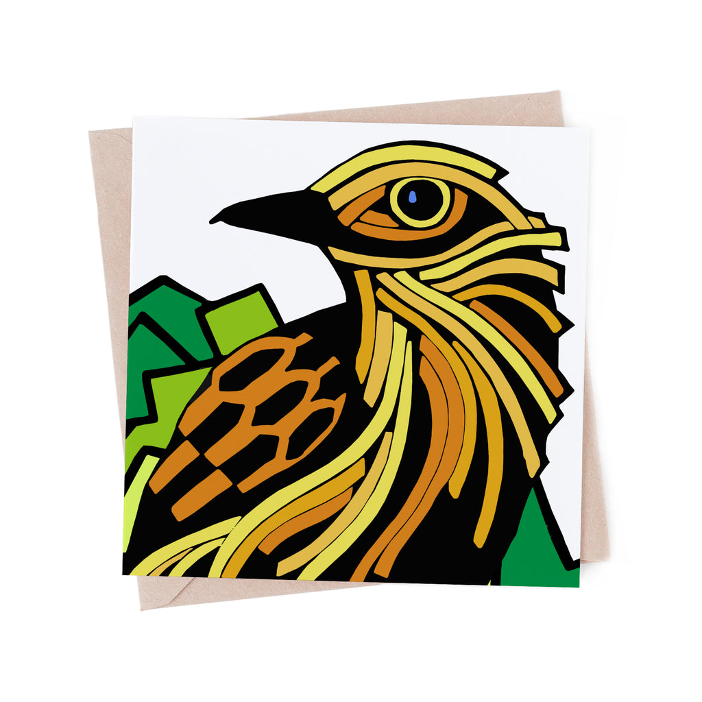Square greeting card with a stylized, yellow bird with a green tree. There is a brown envelope in the background.