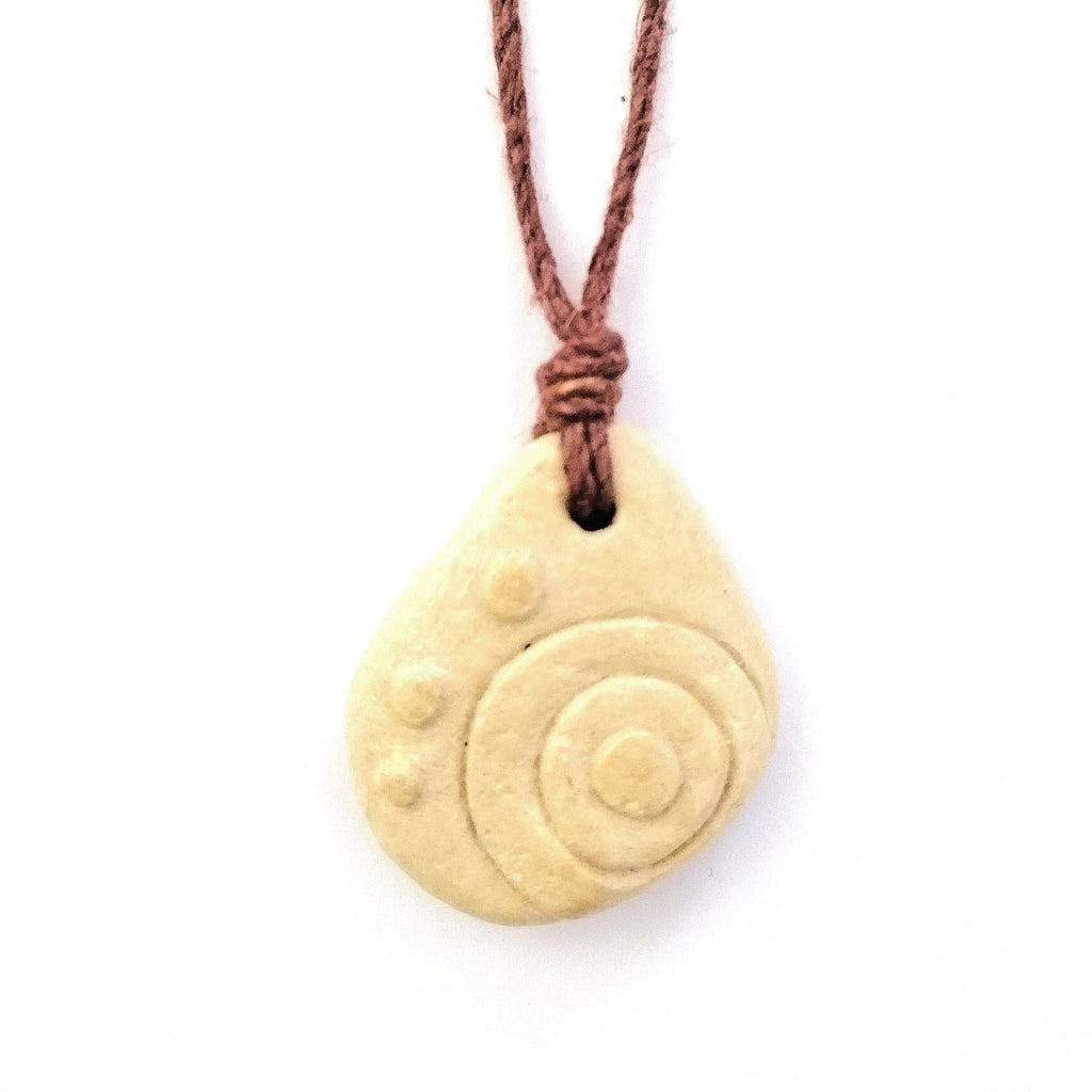 Limestone pendant on hemp string necklace with a copper bead. Discs and dots are carved on the front of the Maltese pebble
