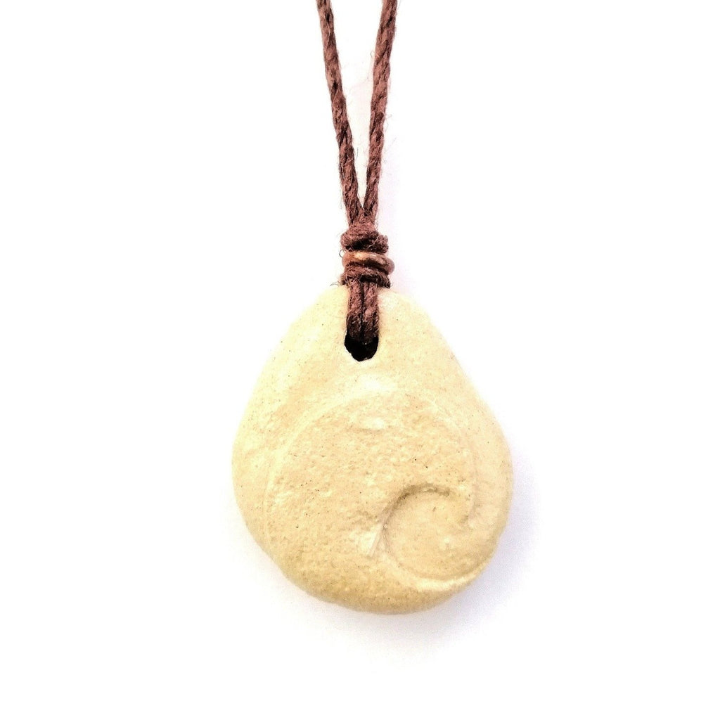 Limestone pendant on hemp string necklace with a copper bead. A wave is carved on the front of the drop shaped pebble