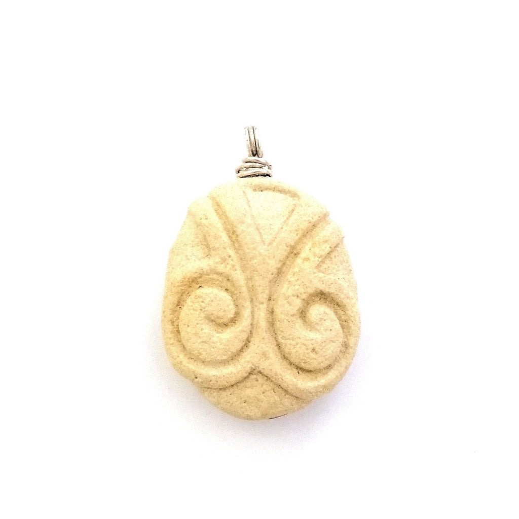 Limestone pendant with sterling silver wire. Two spirals are carved on the front of the whitish, yellowish stone from Malta.