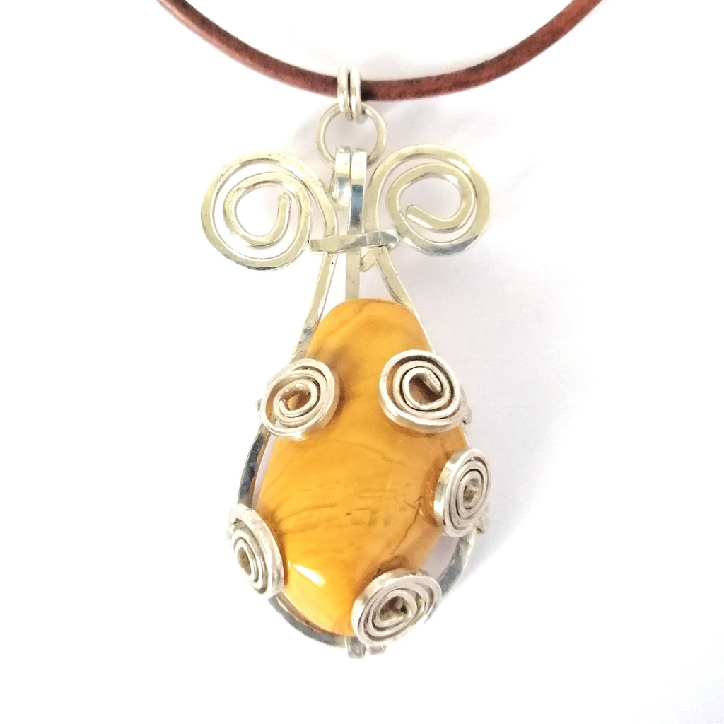 Drop shaped yellow jasper and sterling silver pendant on leather cord. Closeup shows the semi precious stone's unique design.