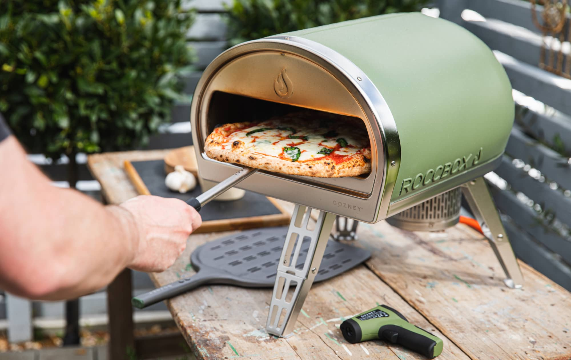 Someone tends to a pizza in the Gozney Roccbox pizza oven