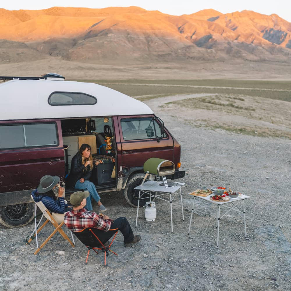 A high vantage shot of a group of friends sitting round and relaxing next to their van as a pizza cooks in the Gozney Roccbox pizza oven