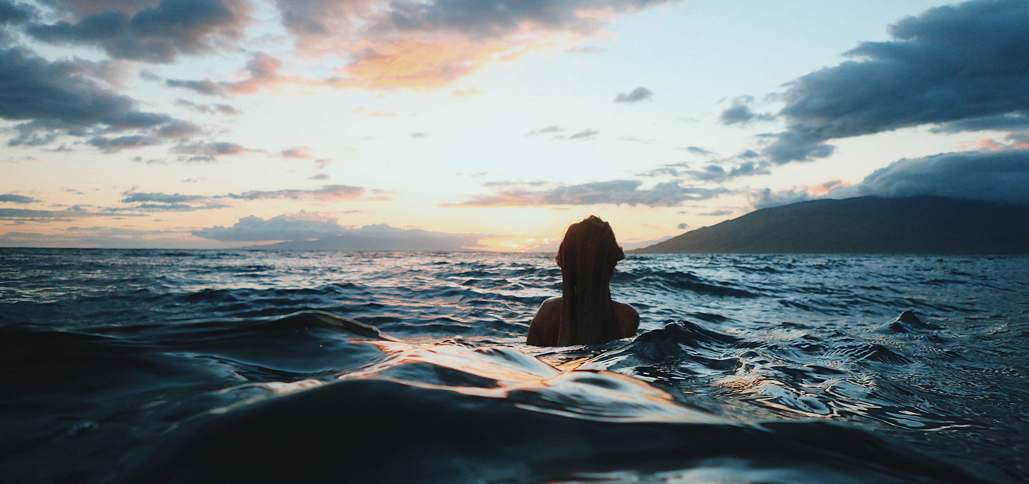 Woman takes a cold dip in the ocean.