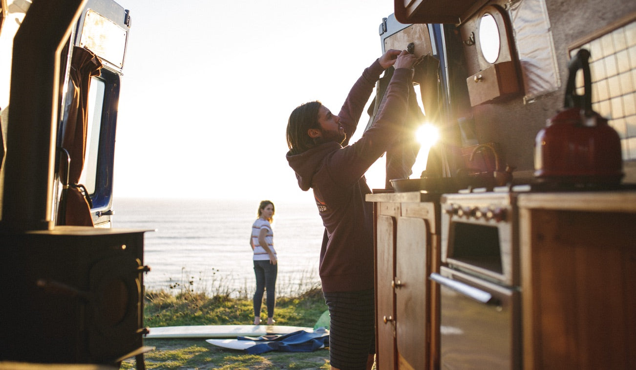 A couple enjoy a sunset view over the ocean fromm their quirky camper