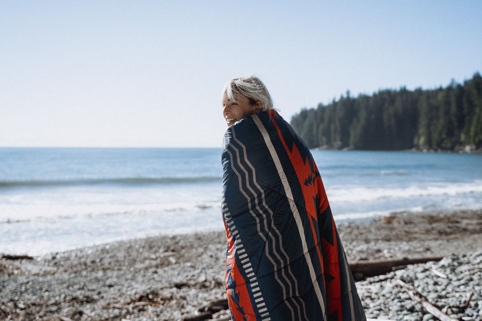 A woman wraps herself in a 2 person Nomadic blanket on a beach surrounded by trees