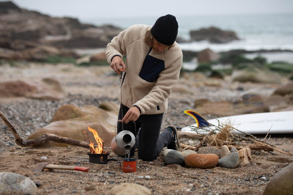 A man wearing the offgrid fleece makes himself a coffee over a campfire