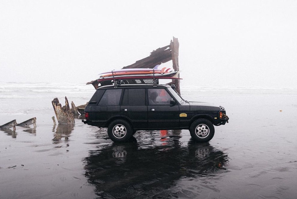 A 4x4 sits parked on a beach next to a giant piece of drift wood