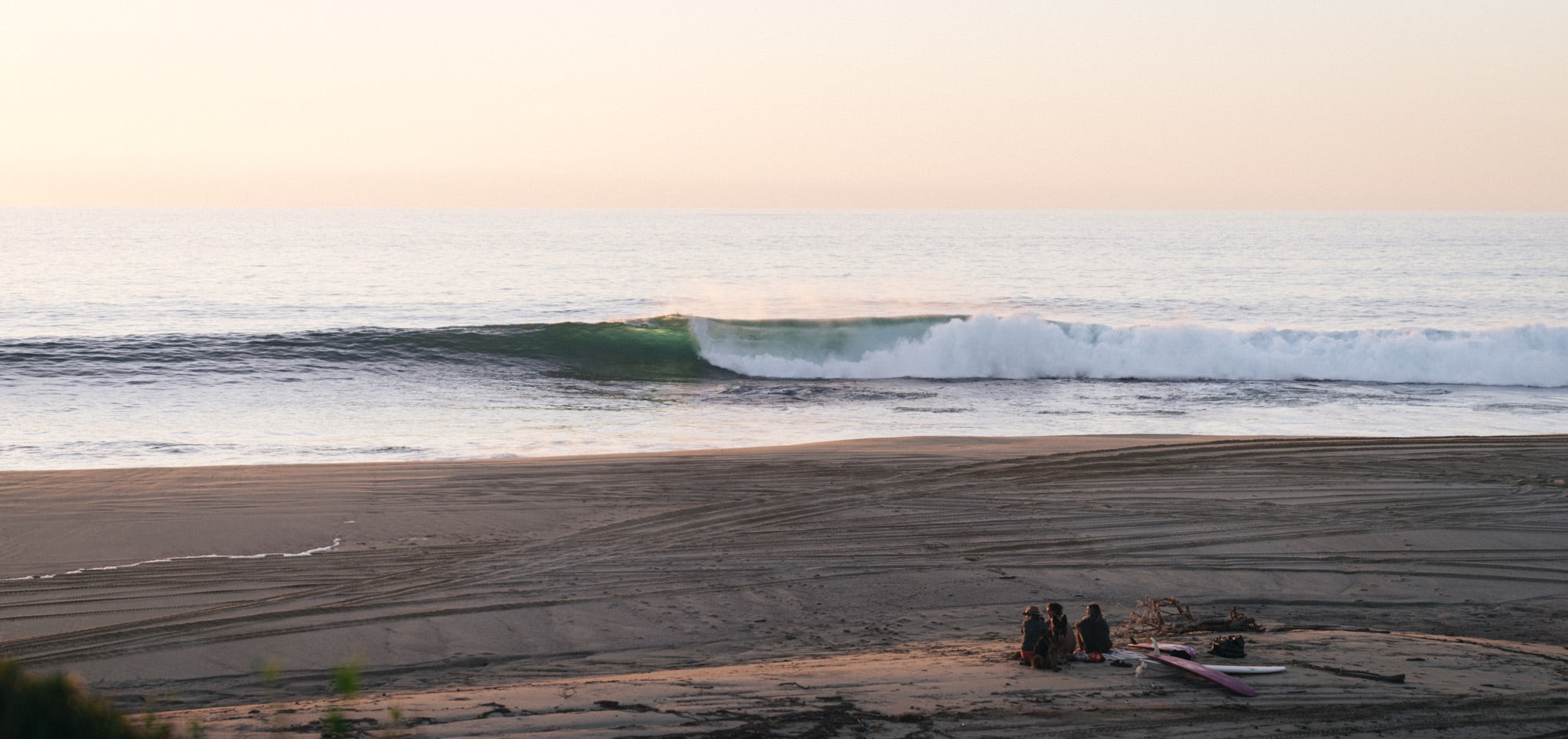 A group of friends sit on the beach at dusk as a perfect wave rolls through