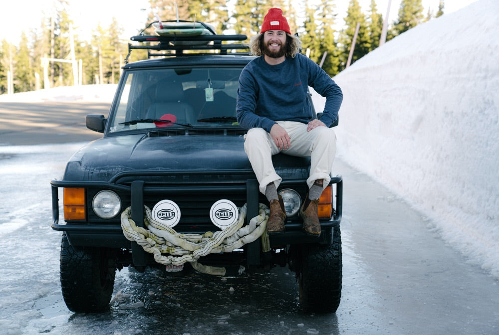 Brandon Haley sits on the bonnet of his 4x4 on a snowy road in the Pacific NorthWest