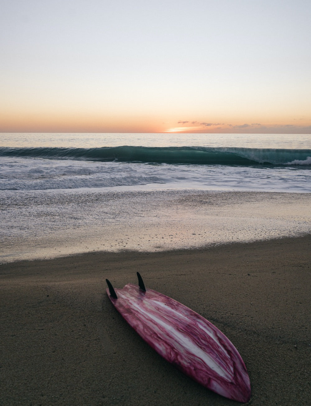 A twin fin surfboard lays in the sand at sunset as a wave breaks in the background