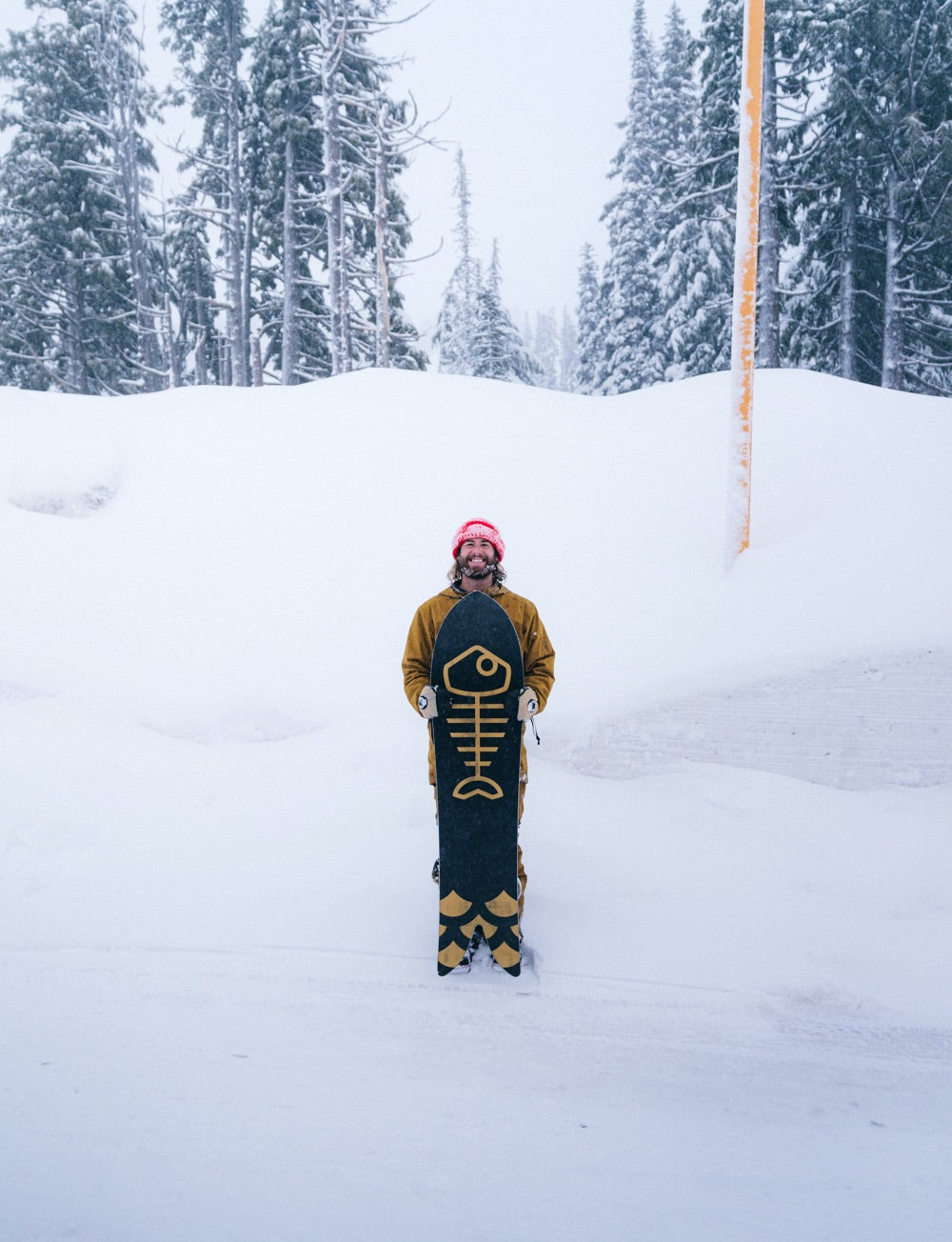 Brandon Haley stands on the side of a road holding his snowboard and a big grin, with a snowy forest scene in the background