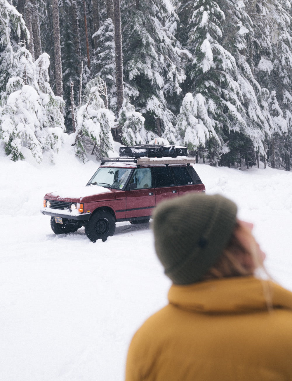 A 4x4 drives through a snow covered road in a forest.