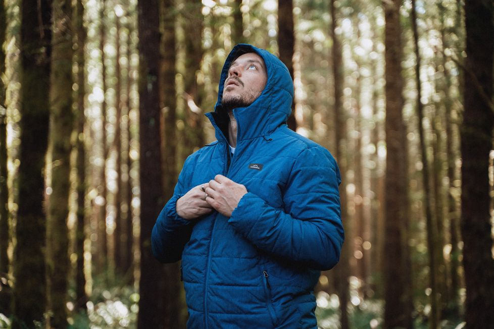 A man stands in a forest looking up at the trees wearing a patrol jacket