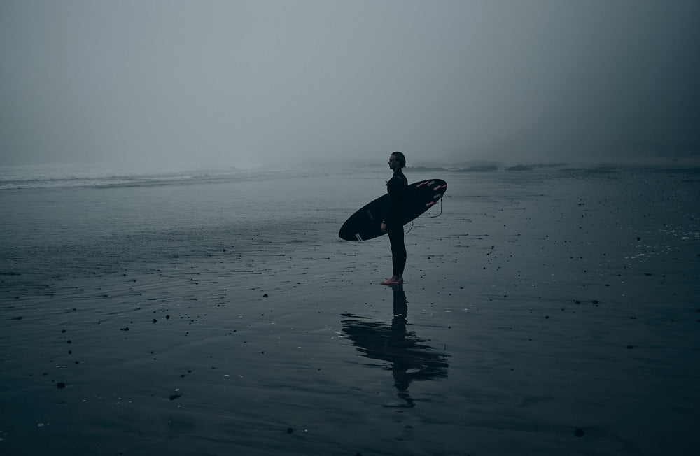Sense of adventure: A surfer stands on the shoreline looking out to see, getting ready to enter the water.