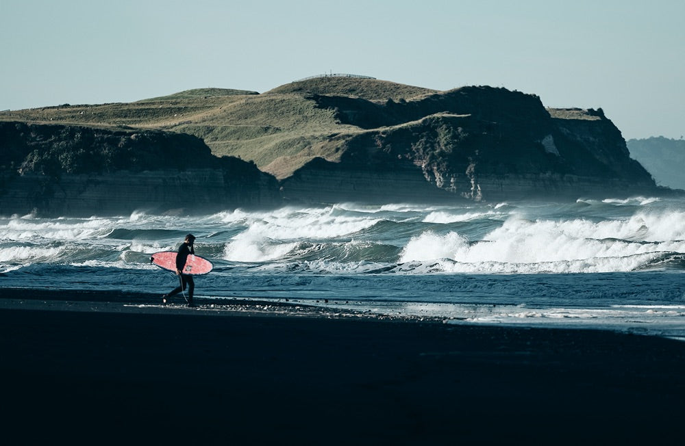Sense of adventure: A surfer walks to the waterline as the waves roll in to shore