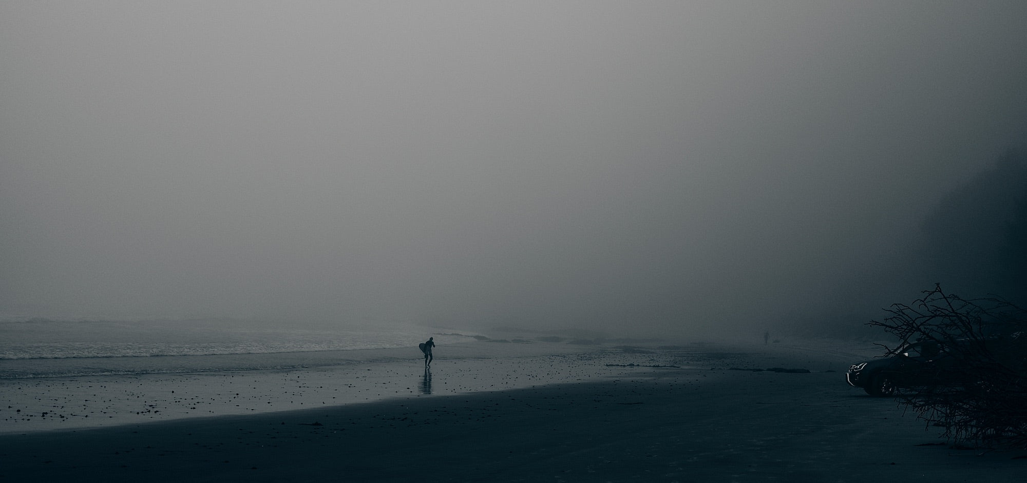 A surfer walks along a beach shrouded in mist as another figure approaches from the distance