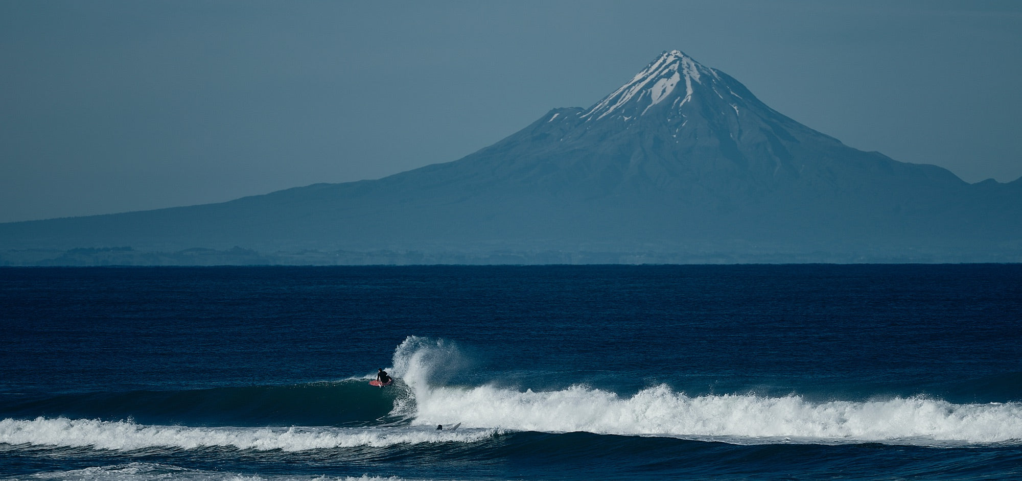 A surfer rides a beautiful wave with a mountain in the distance