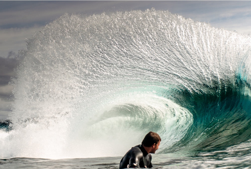 A bodyboarder sits deep in a barelling wave
