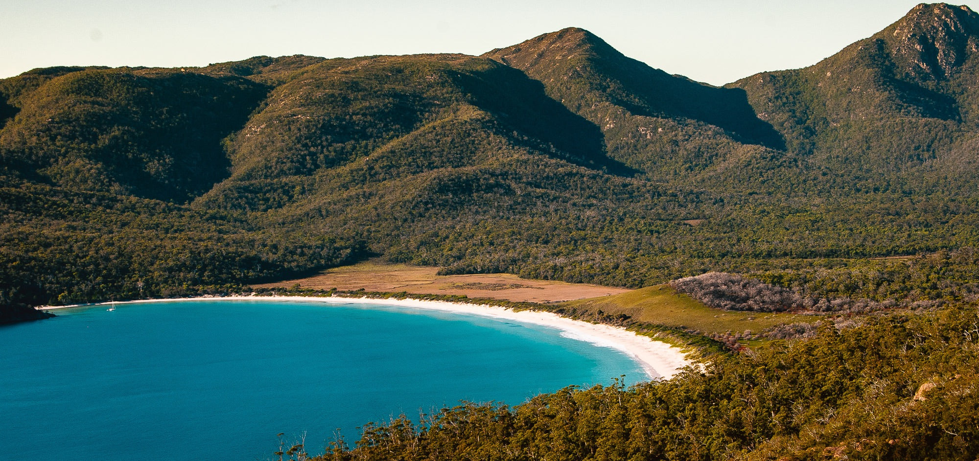 Wineglass Bay - A beautiful white sand beach surrounded by mountains and hills covered in trees with a brilliant blue sea rolling in to the shore.