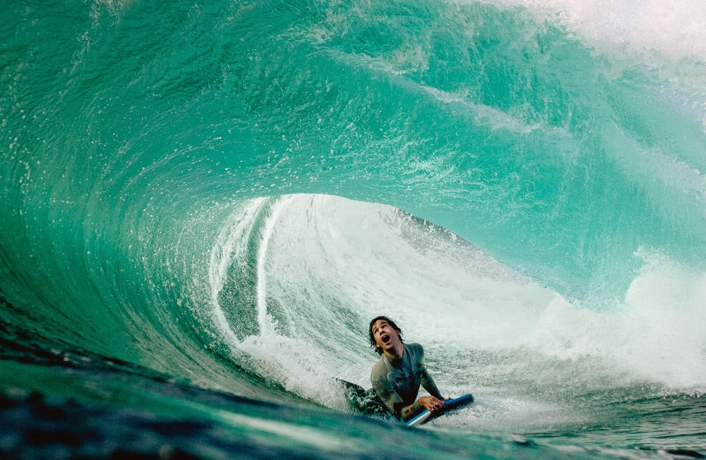 A bodyboarder looks up in awe as a barrelling wave breaks over the top of him.