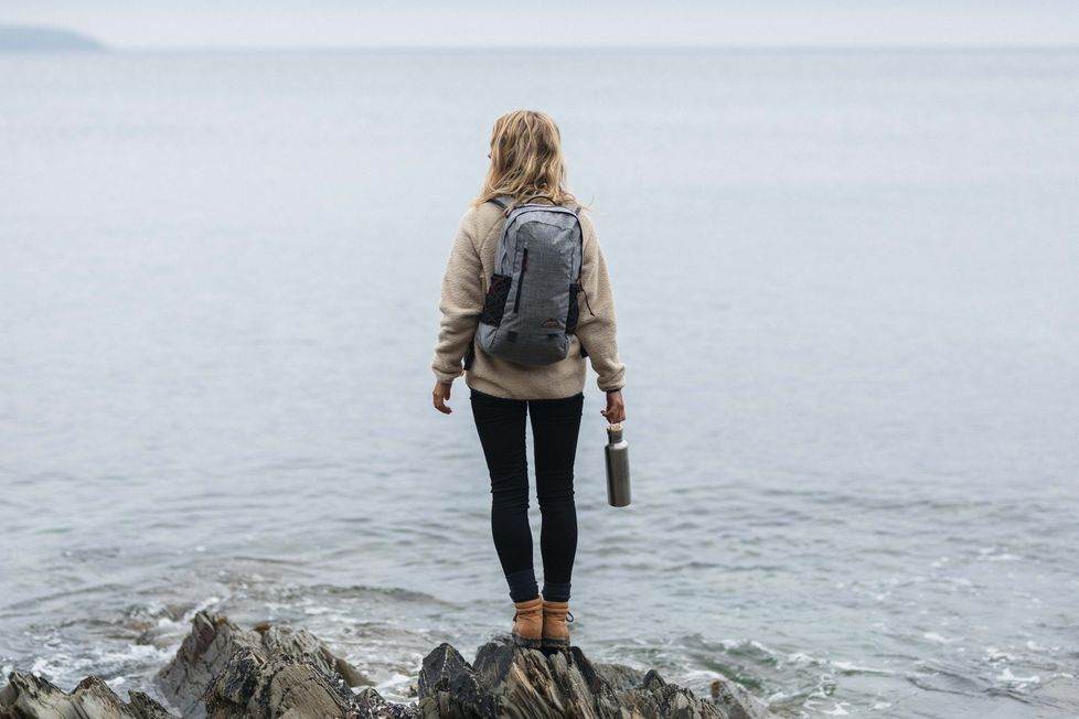 A woman stands on rocks looking out to sea wearing the vale backpack