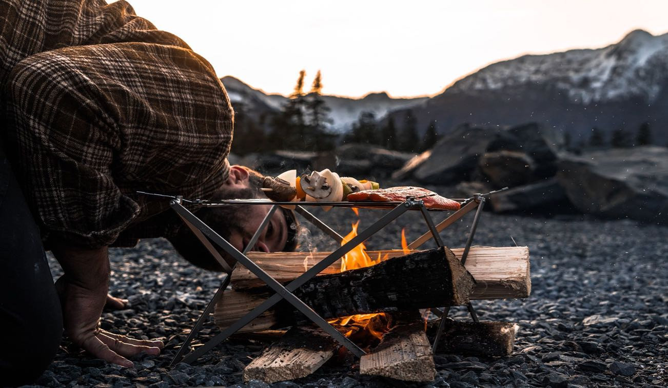 Someone tends to the fire on their Wolf and Grizzly Grill