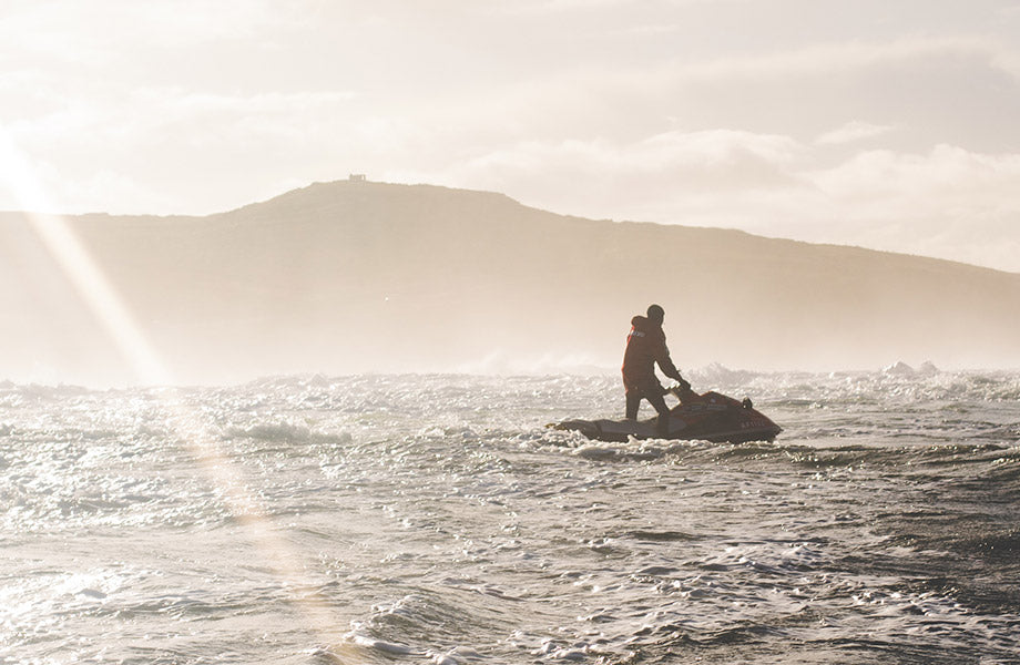 A jet-ski rides off into the distance as the sun begines to set on the irish coastline
