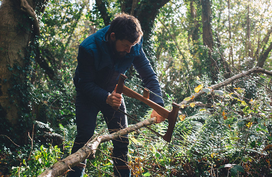 Barry chopping a tree in the woods for logs