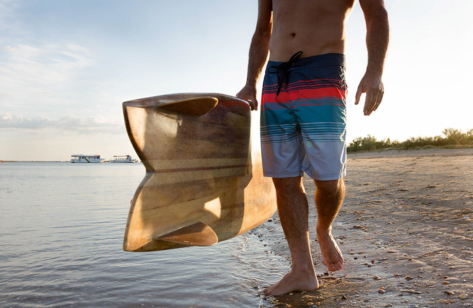 Man wearing hazed boardshorts walking along the beach holding a surfboard
