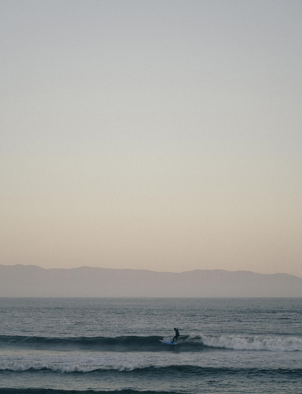 A lone surfer rides the last wave of the day with a hazy dusk horizon in the background